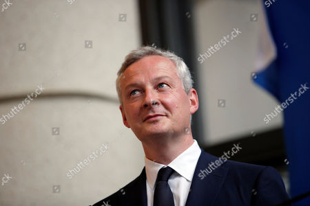 Newly named French economy minister, Bruno Le Maire, 48, left, listens to his predecessor, Michel Sapin, during an handover ceremony in Paris, France, . The crucial Economy Ministry will be run by prominent conservative Bruno Le Maire, an important gesture to the right-wing Republicans party ahead of parliamentary elections next month