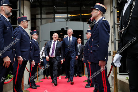 Newly named French economy minister, Bruno Le Maire, 48, right, walks with his predecessor, Michel Sapin, after an handover ceremony in Paris, France, . The crucial Economy Ministry will be run by prominent conservative Bruno Le Maire, an important gesture to the right-wing Republicans party ahead of parliamentary elections next month