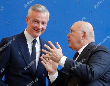 Newly named French economy minister, Bruno Le Maire, 48, left, acknowledges applause from his predecessor, Michel Sapin, during an handover ceremony in Paris, France, . The crucial Economy Ministry will be run by prominent conservative Bruno Le Maire, an important gesture to the right-wing Republicans party ahead of parliamentary elections next month