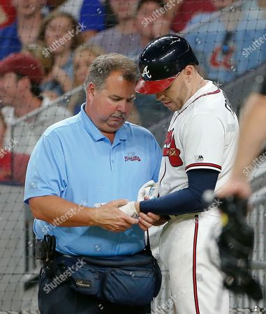 Freddie Freeman, Jim Lovell Atlanta Braves first baseman Freddie Freeman (5) has his hand examined by trainer Jim Lovell after he was hit by a pitch from Toronto Blue Jays relief pitcher Aaron Loup (62) in the fifth inning of a baseball game, in Atlanta. Freeman left the game