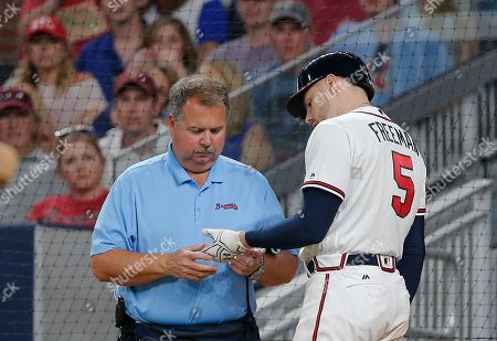 Atlanta Braves first baseman Freddie Freeman (5) has his hand examined by trainer Jim Lovell after he was hit by a pitch in the fifth inning of a baseball game against the Toronto Blue Jays, in Atlanta