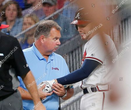 Stock Photo of Atlanta Braves first baseman Freddie Freeman (5) has his hand examined by trainer Jim Lovell after he was hit by a pitch in the fifth inning of a baseball game against the Toronto Blue Jays, in Atlanta