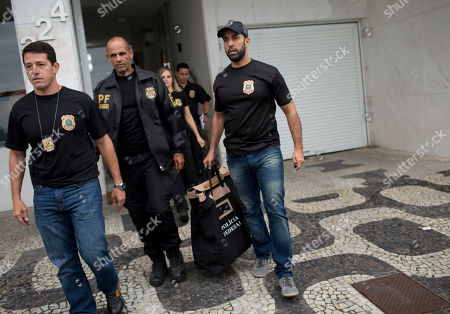 """Federal police officers leave the building where Brazilian Senator Aecio Neves resides, at Ipanema beach in Rio de Janeiro, Brazil, . Brazilian federal police are searching the office and homes of Neves, a top senator and presidential contender. He is being investigated in several corruption cases related to the """"Car Wash"""" probe into kickbacks to politicians. He has denied wrongdoing"""