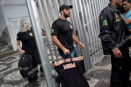 """Federal police officers, carrying seized items, leave the building where Brazilian Senator Aecio Neves resides, at Ipanema beach in Rio de Janeiro, Brazil, . Brazilian federal police are searching the office and homes of Neves, a top senator and presidential contender. He is being investigated in several corruption cases related to the """"Car Wash"""" probe into kickbacks to politicians. He has denied wrongdoing"""