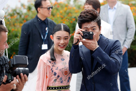 Takuya Kimura, Hanna Sugisaki Actor Takuya Kimura, right, takes a photograph as he poses with actress Hanna Sugisaki during the photo call for the Blade of the Immortal, at the 70th international film festival, Cannes, southern France