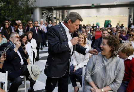 """Frankie Avalon surprises a woman in the audience before singing """"Venus"""" below a 92-foot stainless steel Venus sculpture during the opening ceremony of the Piazza Angelo, in San Francisco. The sculpture in the piazza at Trinity Place was designed by Lawrence Argent and was a gift to the city from developer Angelo Sangiacomo. The song was Avalon's first number-one hit in 1959"""