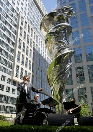 """Frankie Avalon sings """"Venus"""" below a 92-foot stainless steel Venus sculpture during the opening ceremony of the Piazza Angelo, in San Francisco. The sculpture in the piazza at Trinity Place was designed by Lawrence Argent and was a gift to the city from developer Angelo Sangiacomo. The song was Avalon's first number-one hit in 1959"""