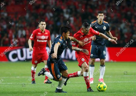 Stock Picture of Chivas' Michael Perez, left, fight for the ball with Toluca's Rubens Sambueza during a Mexico soccer league semifinal first leg match at Nemesio Diez Stadium in Toluca, Mexico