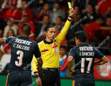 Referee Oscar Macias Romo awards a yellow card to Chivas' Jesus Sanchez, right, as teammate Carlos Salcido points the other way during a Mexico soccer league semifinal first leg match at Nemesio Diez Stadium in Toluca, Mexico