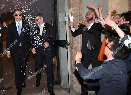 Italian Undersecretary of State Ivan Scalfarotto (2-L) and his partner Federico (L) leave the registry office at the end of their wedding ceremony after receiving rice from their friends at the Palazzo Reale in Milan, 20 May 2017. Italian Undersecretary of State Ivan Scalfarotto is the first Italian government member who is using the new Civil Union rules.