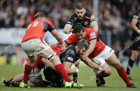 Geoff Parling of Exeter Chiefs is tackled by Jackson Wray of Saracens and Jamie George of Saracens with Schalk Burger of Saracens in support during the Aviva Premiership semi final match between Exeter Chiefs and Saracens at Sandy Park on May 20th , Exeter, Devon.