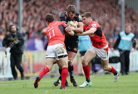 Geoff Parling of Exeter Chiefs is tackled by Chris Wyles and Owen Farrell of Saracens