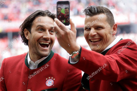 Former Bayern Munich's Luca Toni, left, and Daniel van Buyten make a selfie prior to the German first division Bundesliga soccer match between FC Bayern Munich and SC Freiburg at the Allianz Arena stadium in Munich, Germany