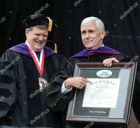 Michael Pence, Robert Graham Vice President Michael Pence points to the honorary degree presented to him as college provost Robert Graham, at the commencement ceremony at Grove City College in Grove City, Pa