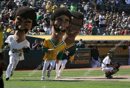 Mascots representing former Oakland Athletics Dennis Eckersley, from left, Rollie Fingers and Rickey Henderson race during a baseball game between the Athletics and the Boston Red Sox in Oakland, Calif