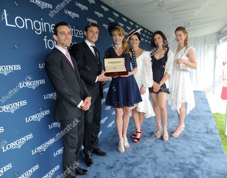 Stock Image of Ramon Dominguez, Gaetan Audier, Jennifer Winslow, Michelle Payne, Reed Kessler, Nicole Stronach Walker Hall of Fame Award Winning Jockey Ramon Dominguez, Longines' Gaetan Audier, Australian jockey Michelle Payne, American show jumper Reed Kessler and Host of the Preakness Nicole Stronach Walker, left to right, present Jennifer Winslow, center, with a Longines DolceVita timepiece after she won the Longines Prize for Elegance at the Preakness Stakes, at Pimlico Race Course in Baltimore. Longines, the Swiss watch manufacturer known for its elegant timepieces, is the Official Watch and Timekeeper of the 142nd annual Preakness Stakes and the Triple Crown