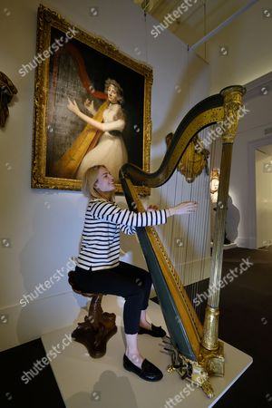 Stock Photo of  A Sotheby's staff member plays a late Recency painted and guilted harp (set 1820) byJacob and James Erat with an estimate of £1,2000-£1,500. The collection of objects are from the Belgravia home of Lord Ballyedmond are presented in the Sotheby's auction house sale which recalls the aristocratic London town house.