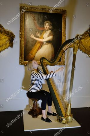Stock Picture of  A Sotheby's staff member plays a late Recency painted and guilted harp (set 1820) byJacob and James Erat with an estimate of £1,2000-£1,500. The collection of objects are from the Belgravia home of Lord Ballyedmond are presented in the Sotheby's auction house sale which recalls the aristocratic London town house.