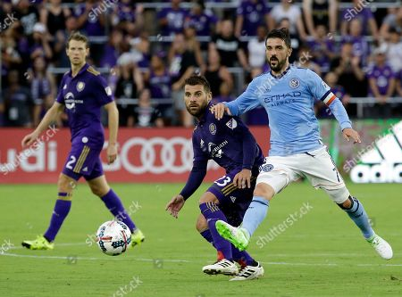 New York City FC's David Villa (7) clears the ball away from Orlando City's Antonio Nocerino (23) during the first half of an MLS soccer game, in Orlando, Fla