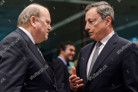 Ireland's Finance Minister Michael Noonan, left, talks with the President of the European Central Bank Mario Draghi prior to a meeting of Eurogroup finance ministers at the EU Council building in Brussels