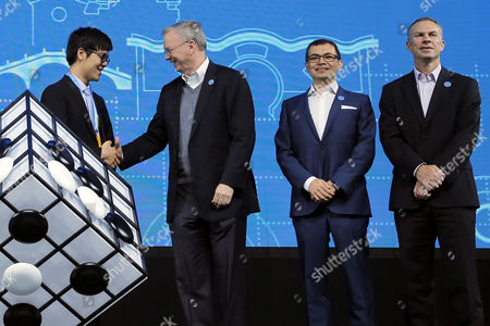 Chinese Go player Ke Jie (L) shakes hands with Alphabet executive chairman Eric Schmidt (2-L) beside Demis Hassabis (2-R), co-founder of Google's artificial intelligence (AI) startup DeepMind and Scott Beaumont (R), President of Google Greater China, during the opening ceremony of the Future of Go summit ahead of a match between Ke Jie and Google's artificial intelligence program AlphaGo at Wuzhen internet international conference and exhibition center in Wuzhen, China's Zhejiang province, 23 May 2017. The summit is held from 23 to 27 May in Wuzhen.