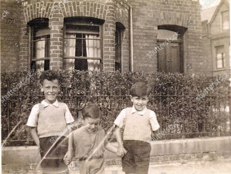 Ethnic Cleansing In Northern Belfast...where Despite The Intense Political Effort The Separation Of Communities Seems To Be Getting Worse. Feature By Es Writer Cal Mccrystals' Return To Belfast... Picture Shows..collect Picture Of Writer Cal Mccrystal(far Right)with His Brothers Coln And Brendan In Belfast. 1941.