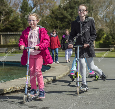 Stock Photo of Parents Remove Their Children From School Across The UK In A Day Of Action Against Children Being Over-tested In The School System. (l To R) Megan Bennett 7 And Grace Bennett 10 Scoot Around Stanley Park Blackpool Lancs. With Their Parents On Their Day Off From Attending School. - 3/5/16.
