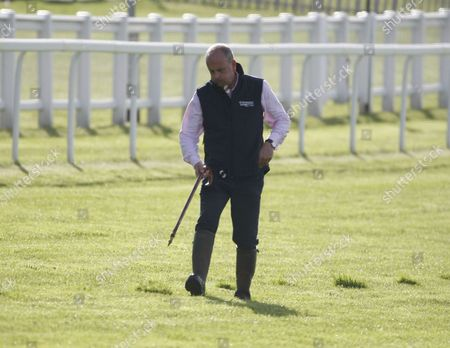 Andrew Cooper, clerk of the Course replaces divots  at the iconic Breakfast with the Stars preview of the world famous Classic Derby horse race on the Downs above the town.