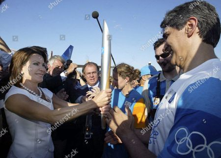 Athens 2004 Olympic Games Organizing Committee President Gianna Angelopoulos-daskalaki (l) Hands Over the Olympic Torch to Veteran Basketball Player Panagiotis Giannakis (r) who Will Be the First Torchbearer of the Olympic Relay in Greece Friday July 09 2004 Also in the Photo Athens 2004 Executive Director Marton Simitsek (2nd L) and Industrialist Theodoros Angelopoulos Husband of Gianna Angelopoulos-daskalaki Greece Iraklion
