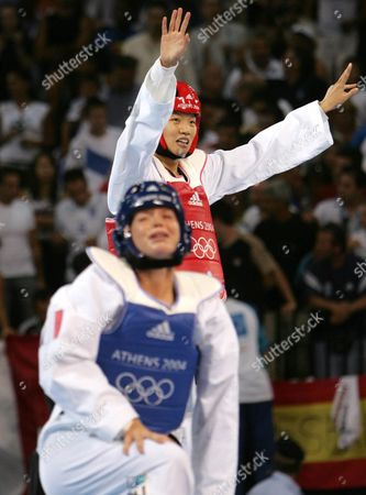 Stock Picture of China's Zhong Chen (rear) Celebrates Her Victory Over France's Myriam Baverel (foreground) in the Final Bout of the Women's +67 Kg Taekwondo Category of the Athens 2004 Olympic Games Sunday 29 August 2004 Greece Athens