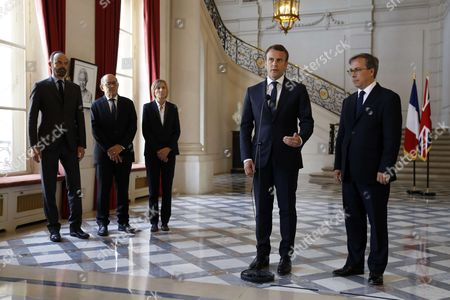 French President Emmanuel Macron (2ndR) and English ambassador Edward Llewellyn (R) deliver a speech next to French Prime Minister Edouard Philippe (L), French Foreign Affairs Minister Jean-Yves Le Drian (2ndL) and French Minister for European Affairs Marielle de Sarnez (C) after French President signed the condolences book at the English Embassy in Paris, France. This meeting takes place after the Manchester bombing
