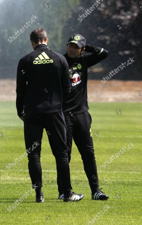 The manager of Chelsea Football Club - Antonio Conte (in conversation with Carlo Cudicini) watches his players train