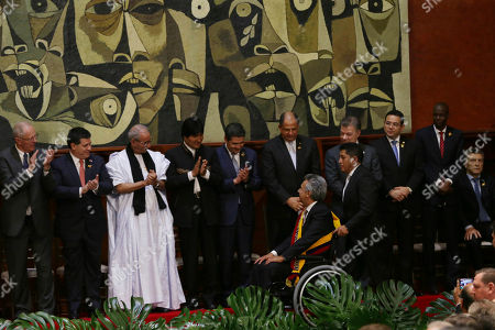 Lenin Moreno past the line of regional heads of state: Peru's Pedro Pablo Kuczynski; from left to right, Paraguay's Horacio Cartes; Bolivia's Evo Morales; Juan Orlando Hernandez of Honduras; Costa Rica's Luis Guillermo Solis; Colombia's Juan Manuel Santos; Guatemala's Jimmy Morales; Haiti's Jovenel Moise; and Argentina's Maurico Macri Ecuador's incoming President Lenin Moreno is pushed in his wheelchair past a line of regional heads of state, from left to right; Peru's Pedro Pablo Kuczynski; Paraguay's Horacio Cartes; Bolivia's Evo Morales; Juan Orlando Hernandez of Honduras; Costa Rica's Luis Guillermo Solis; Colombia's Juan Manuel Santos; Guatemala's Jimmy Morales; Haiti's Jovenel Moise; and Argentina's Maurico Macri, at the end of the swearing in ceremony in the National Assembly, in Quito, Ecuador, . Moreno was sworn into office Wednesday after narrowly defeating a conservative former banker in last month's runoff. National Assembly