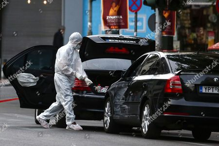 Greek police experts search for evidence at the scene of an explosion site in Athens, on .An explosion inside a car in Greece's capital wounded former Prime Minister Lucas Papademos on Thursday, police said. His injuries were not considered to be life-threatening
