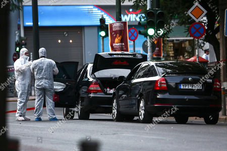 Greek police experts search for evidence at the scene of an explosion, in Athens, . An explosion inside a car in Greece's capital wounded former Prime Minister Lucas Papademos on Thursday, police said. His injuries were not considered to be life-threatening