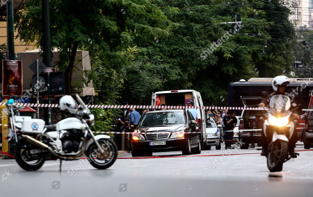 Members of the emergency services on the scene of an explosion site in Athens, . An explosion inside a car in Greece's capital wounded former Prime Minister Lucas Papademos on Thursday, police said. His injuries were not considered to be life-threatening