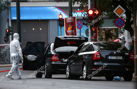 Greek police experts search for evidence at the scene of an explosion site in Athens, on . An explosion inside a car in Greece's capital wounded former Prime Minister Lucas Papademos on Thursday, police said. His injuries were not considered to be life-threatening