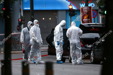 Greek police experts search for evidence at an explosion site in Athens, on .An explosion inside a car in Greece's capital wounded former Prime Minister Lucas Papademos on Thursday, police said. His injuries were not considered to be life-threatening