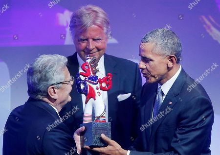 Former US President Barack Obama is awarded the German Media Prize 2016 by Media Control founder Karlheinz Koegel, center, and former German President Joachim Gauck, left, in Baden-Baden, Germany