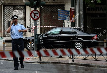 A policeman stands in a cordoned off area around a Mercedes car of former Greek Prime Minister Lucas Papademos after an explosion inside the car caused by a bomb attack in central Athens, Greece, 25 May 2017. Lucas Papademos, his driver and one other person was injured in the blast. According to the first reports, the explosion was caused by a booby-trapped envelope that went off while the car was in motion. The initial images indicate that the car suffered major damage. There was also a second car escorting the former premier.
