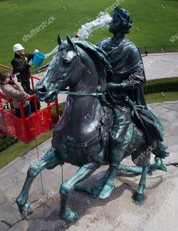 A worker washes a city landmark, the equestrian statue of Peter the Great known as the Bronze Horseman by French sculptor Etienne Maurice Falconet, in St.Petersburg, Russia