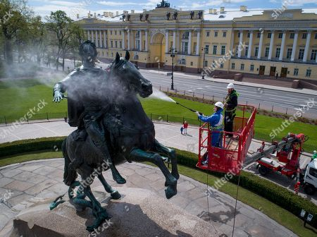 A worker washes a city landmarks, the equestrian statue of Peter the Great known as the Bronze Horseman by French sculptor Etienne Maurice Falconet, in St.Petersburg, Russia