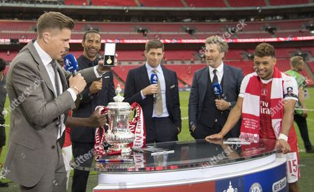 The winner's medal of Alex Oxlade-Chamberlain of Arsenal as he is interviewed after the match by, l-r, BT Sport's Jake Humphreys, Rio Ferdinand, Steven Gerrard and Robbie Savage after the match