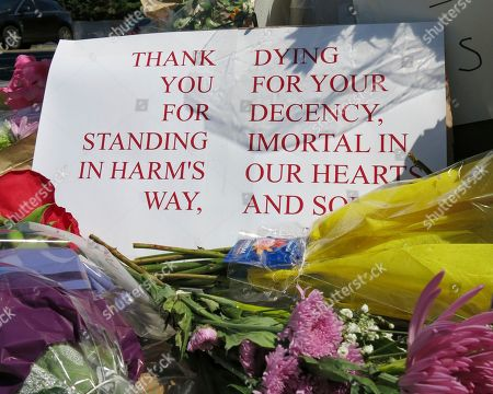 A sign of thanks rests against a traffic light pole at a memorial outside the transit center in Portland, Ore. on . People stopped with flowers, candles, signs and painted rocks for two bystanders who were stabbed to death Friday, while trying to stop a man who was yelling anti-Muslim slurs and acting aggressively toward two young women, including one wearing a Muslim head covering, on a light-trail train in Portland. Suspect Jeremy Joseph Christian, 35, was booked on suspicion of murder and attempted murder in the attack and will make a first court appearance Tuesday