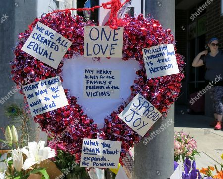 A heart-shaped wreath covered with positive messages hangs on a traffic light pole at a memorial for two bystanders who were stabbed to death Friday, while trying to stop a man who was yelling anti-Muslim slurs and acting aggressively toward two young women, including one wearing a Muslim head covering, on a light-trail train in Portland, Ore, . A memorial grew all day Saturday outside the transit center in Portland, as people stopped with flowers, candles, signs and painted rocks. Jeremy Joseph Christian, 35, was booked on suspicion of murder and attempted murder in the attack