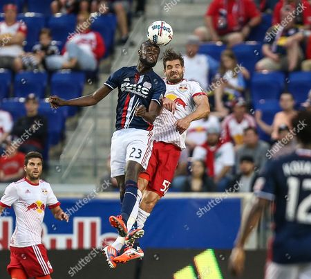 New England Revolution forward Kei Kamara (23) and New York Red Bulls defender Damien Perrinelle (55) fight for the ball during an MLS game between the New England Revolution and the New York Red Bulls at Red Bull Arena in Harrison, NJ. New York won, 2-1