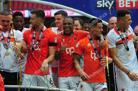 Will Aimson of Blackpool, Andy Taylor of Blackpool and Christian N'Guessan of Blackpool, celebrates after winning during the Skybet League 2 Playoff Final between Blackpool and Exeter City at Wembley Stadium in London, UK on May 28.