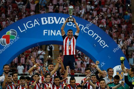 Chivas' Carlos Salcido holds the trophy as the team celebrates its win over Tigres for the Mexican soccer league championship in Guadalajara, Mexico