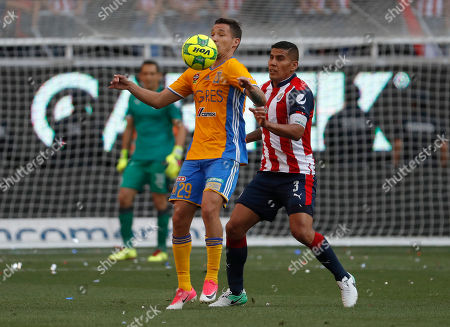 Tigres' Jesus Duenas, front, fights fro the ball with Chivas' Carlos Salcido during the Mexican soccer league final match in Guadalajara, Mexico