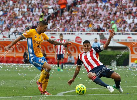 Tigers' Victor Sosa, left, fights for the ball with Chivas' Carlos Salcido during the Mexican soccer league final match in Guadalajara, Mexico